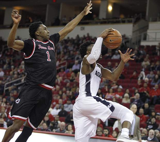 Fresno State's Jaron Hopkins goes in to block the shot of Utah State's Koby McEwen during the second half of an NCAA college basketball game in Fresno, Calif., Saturday, Jan. 27, 2018. (AP Photo/Gary Kazanjian)