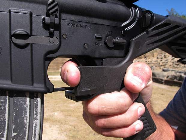 Shooting instructor Frankie McRae demonstrates the grip on an AR-15 rifle fitted with a bump stock at his 37 PSR Gun Club in Bunnlevel, N.C., on Oct. 4.