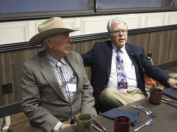 Southern Nevada rancher Cliven Bundy, left, listens to Independent American Party of Nevada Chairman Joel Hansen before Bundy was scheduled to give the keynote address to the third-party's state convention at the Nugget hotel-casino, Friday, Feb. 23, 2018, in Sparks, Nev. Bundy served 700 days in jail before a U.S. judge in Las Vegas threw out the criminal charges against him and others last month stemming from an armed standoff with federal agents at his ranch near Bunkerville in April 2014. (AP Photo/Scott Sonner)