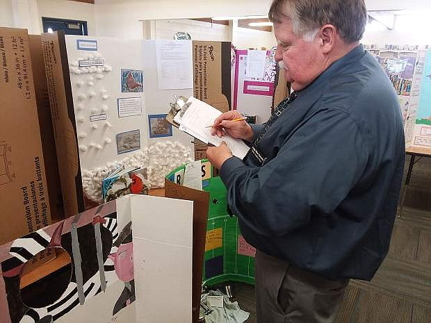 Churchill County Justice Court Judge Mike Richards evaluates student book projects for E.C. Best Elementary School's first Literacy Night on Wednesday.