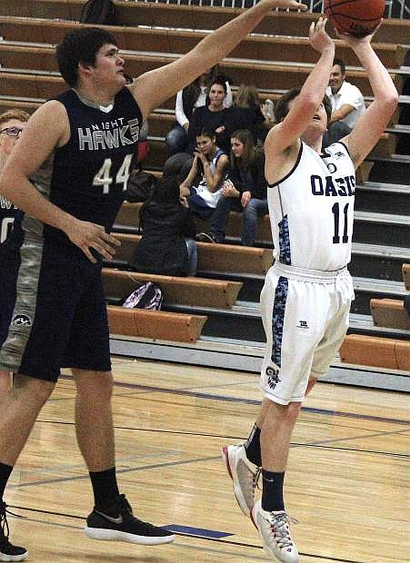 Oasis's Caden Johnson leaps to shoot a basket as Silver Stage's Kevin Kable reaches to block him.