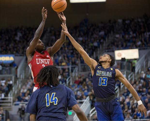 UNLV's Amauri Hardy shoot over Nevada's Hallice Cooke, right, during the first half of an NCAA college basketball game in Reno, Nev., Wednesday, Feb. 7, 2018. (AP Photo/Tom R. Smedes)
