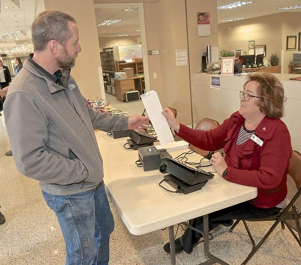 Supervisor Brad Bonkowski checks in for early voting with Deputy Clerk Beth Phelps Thursday at the County Courthouse.