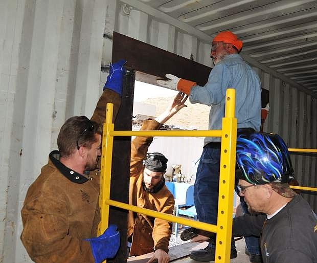 From left, Michael Varner, Charles Carnevale and Eric Forstrom assist Masih Madani, top right, put in a window frame on the home he is building out of a shipping container as part of a welding class project at Western Nevada College.