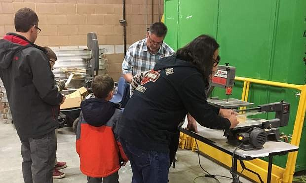 Parents help children shape the shell of their Pinewood Derby racing cars in the Construction Lab at Western Nevada College.
