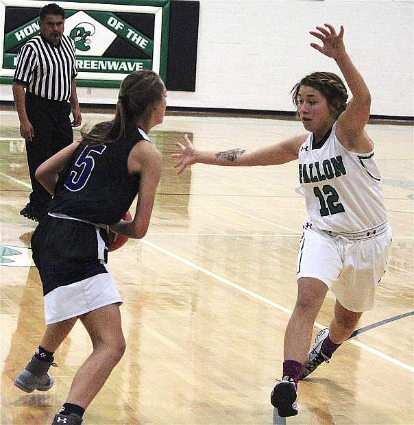 Alexis Jarrett blocks a shot from one of Elko's players during a Fallon home game.