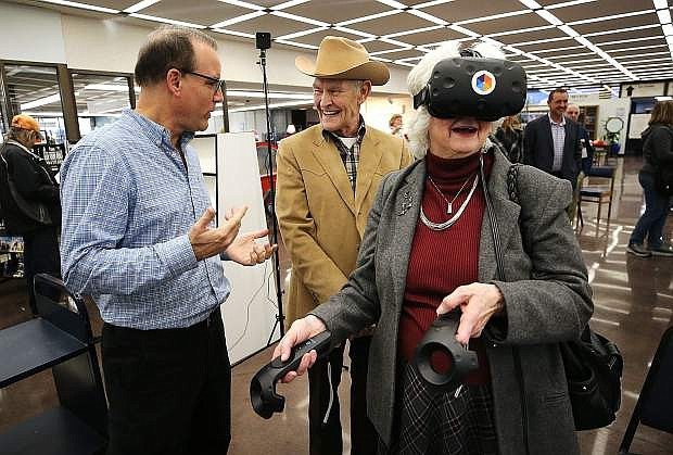 Mark Anderson, with Lifeliqe, teaches Phil and Phyllis Patton about virtual reality during the Grand Reopening Ceremony at the Carson City Library in Carson City, Nev., on Friday, Feb. 16, 2018. Photo by Cathleen Allison/Nevada Momentum