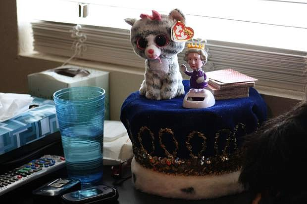 Dilley, who said he is related to royalty, displays his crown and Queen Elizabeth bobblehead given to him by his daughter.