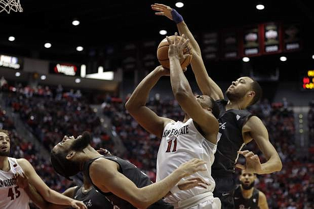 San Diego State forward Matt Mitchell (11), center, shoots as Nevada guard Kendall Stephens (21), right, and forward Cody Martin (11), left, defend during the first half of an NCAA college basketball game Saturday, March 3, 2018, in San Diego. (AP Photo/Gregory Bull)