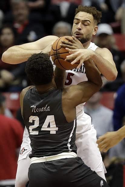 San Diego State's Kameron Rooks blocks a shot by Nevada's Jordan Caroline in the first half Saturday.