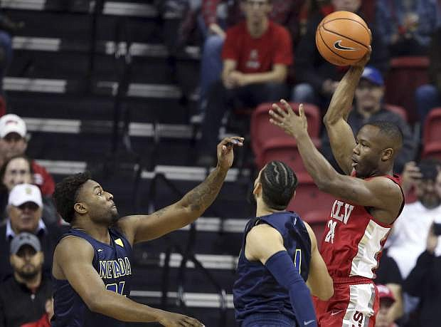 UNLV's Jordan Johnson (24) passes the ball over Nevada's Jordan Caroline, left, and Cody Martin on Feb. 28. UNLV beat Air Force on Wednesday in the Mountain West tournament, setting up a Thursday rematch with the Wolf Pack.