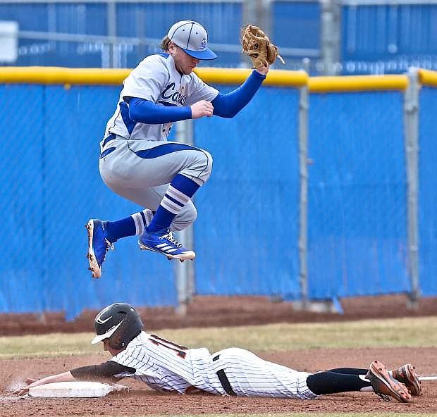 Third baseman Abel Carter jumps above a sliding Sean Dunkelman of Douglas on Saturday at Ron McNutt Field.