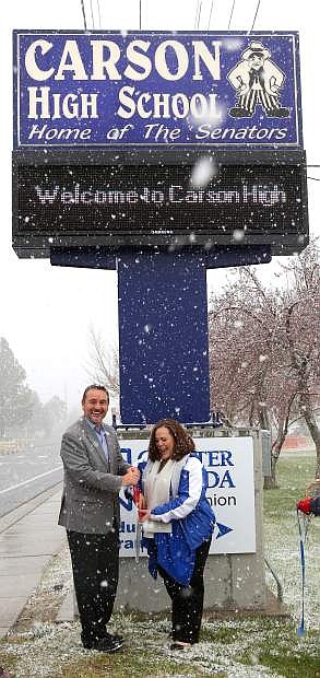 Despite the snow Carson High School Principal Tasha Fuson and Greater Nevada Credit Union President Wally Murray hold a ribbon cutting ceremony on Monday morning to commemorate the installation of a new digital marquee in front of the school. GNCU donated nearly $25,000 to replace the old sign.