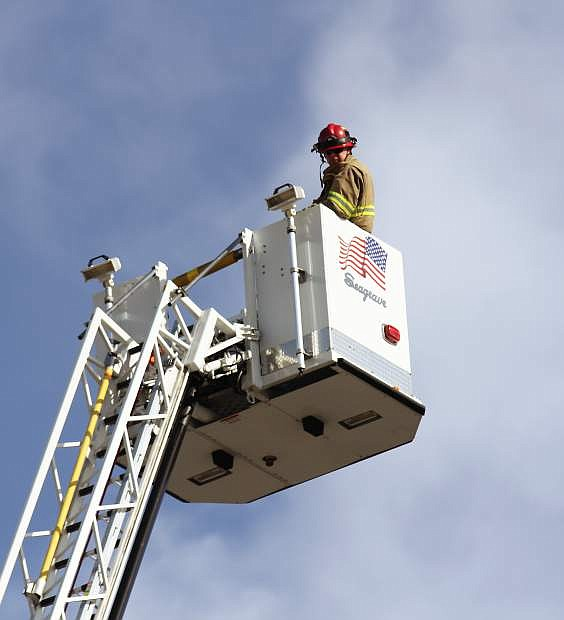 Two firefighters sit in the bucket atop an aerial ladder nearly 100 feet in the air.
