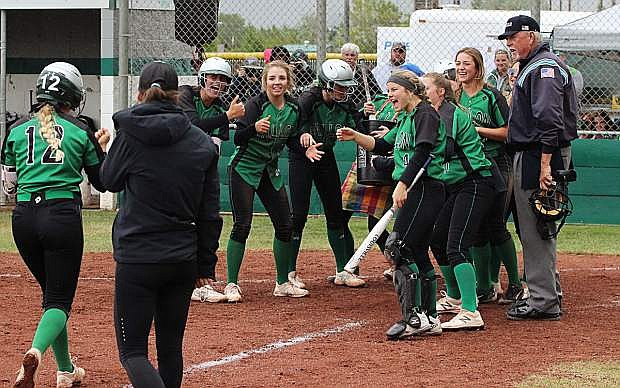 Teammates welcome Stacy Kalt after she hit a game-winning three-run homer in the sixth inning.