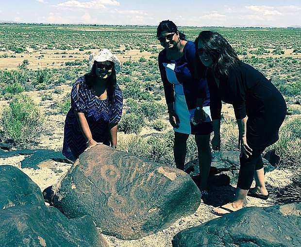 Lynette Fernandes of Seattle, Lyma Fernandes of India and Liz McFarland of Reno examine a petroglyph at Grimes Point near Fallon.