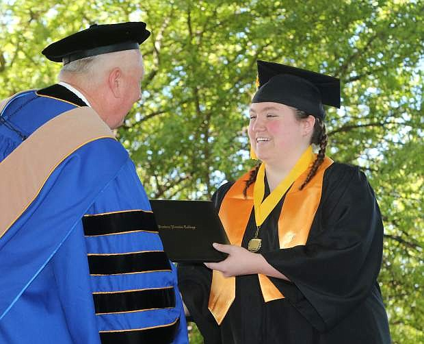 Churchill High School student Malory Pruitt receives her AA degree at the 2017 Western Nevada College commencement ceremony on Monday.