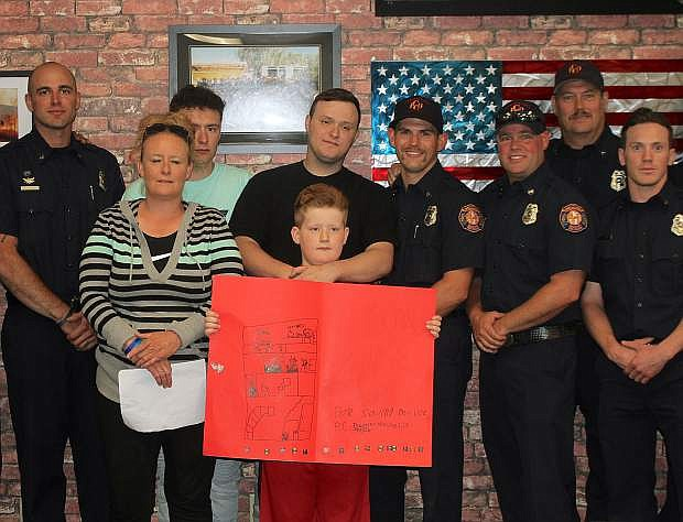Theodore Ntalikas, his mother Lisa Robinson and his brothers Jordan and Sal Leyva stand with some of the firefighters who saved his life in a fire last month.