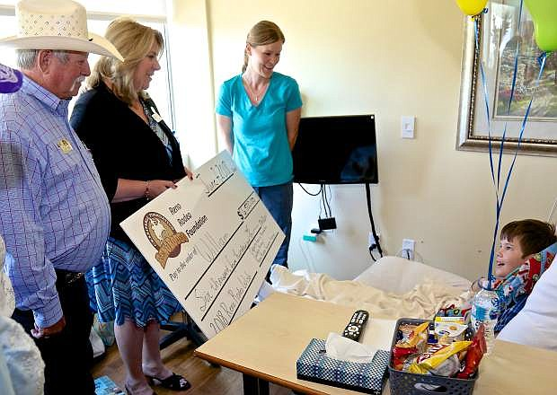 Reno Rodeo Association President Bill Summy and Clara Andriola, Executive Director, present William Strange, 10, a check for $6,500 Thursday at the Carson-Tahoe Hospital's Cancer Treatment Center. Also pictured is William's mother Lora Strange.