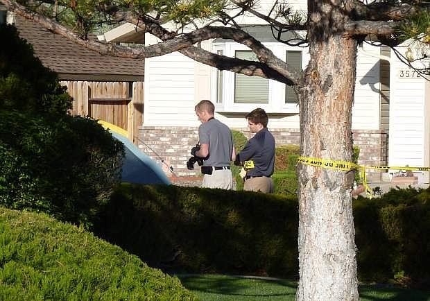 Crime scene investigators gather evidence on Shadow Lane on Sunday morning.