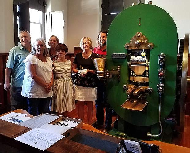 Members of the Churchill County Museum Board pose next to Historic Coin Press No. 1 at the Nevada State Museum in Carson City.