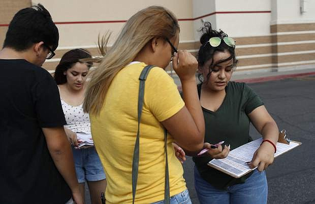 Maria Nieto, right, and Alma Romo, second from left, register people to vote in Las Vegas on Wednesday.