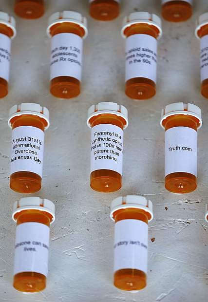 Sam Szoyka, youth program coordinator with Partnership Carson City, builds a display to raise awareness about opioid addiction in Carson City on Wednesday. The 408 prescription bottles, each covered with a statistic about opioid addiction, represent the number of Nevadans who died from an opioid overdose in 2016. The piece can be viewed at Carson and Musser Streets in front of the Capitol.
