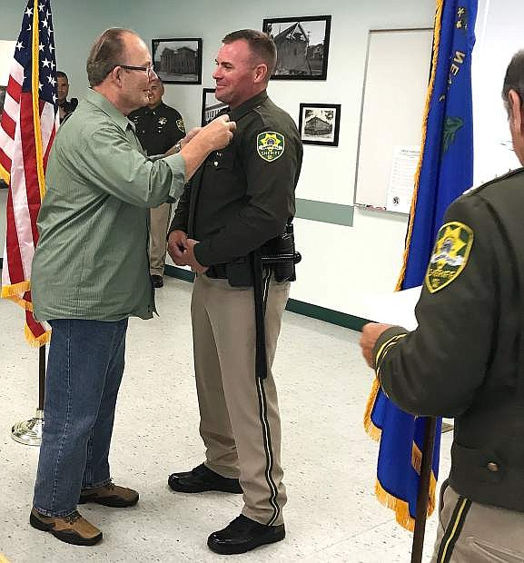 Benjamin Stryffeler's father, John, places his new badge on him.