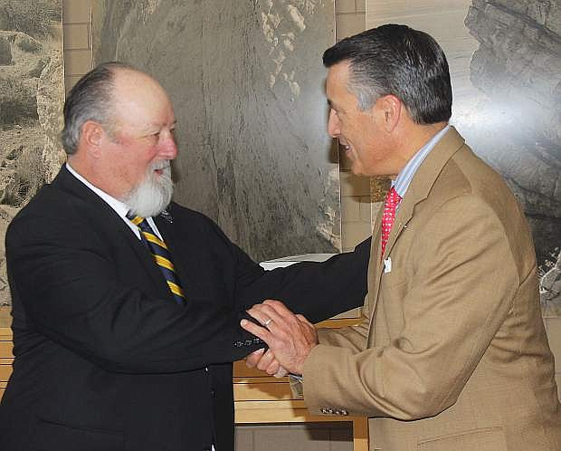 Gov. Brian Sandoval, right congratulates Tom Spencer for being named Veteran of the Month for September.
