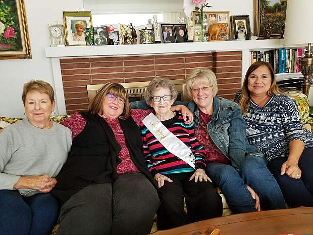 Martha Berger, in the center wearing a sash made for her upcoming birthday party, enjoys a visit with relatives. From left to right, Nina Barry, niece; and Jan Leonard, Dawn Berger, and Lisa Yenter, all grand nieces.