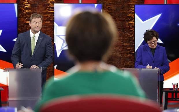 Sen. Dean Heller, R-Nev., left, and Rep. Jacky Rosen, D-Nev., prepare before a U.S. Senate debate, Friday, Oct. 19, 2018, in Las Vegas. (AP Photo/John Locher, Pool)