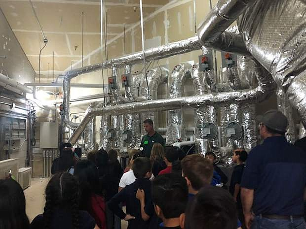 Students at Mark Twain Elementary School tour the bowels of the HVAC (heating, ventilation, and air conditioning) system at their school as they learn about energy efficiency and how they can maximize conservation efforts.