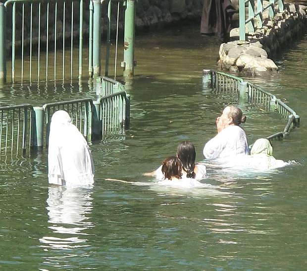 A groups of Russians being baptized in the Jordan River asked that their faces not be shown during the ceremony, and the photographer did his best to oblige.