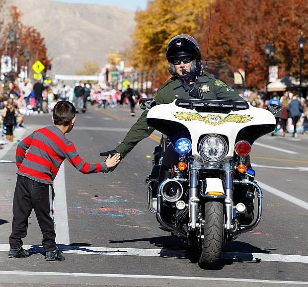 A Carson City Sheriff's Department Motor Patrol gets a high five during the 2017 Nevada Day Parade, Carson City, NV