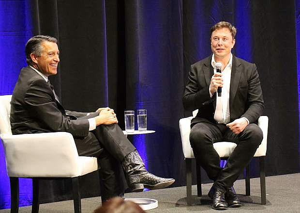 Gov. Brian Sandoval, left, and Tesla CEO Elon Musk share a laugh during a discussion at a technology and innovation summit at the Tesla Gigafactory inside the Tahoe-Reno Industrial Center on Tuesday, Oct. 9, 2018.