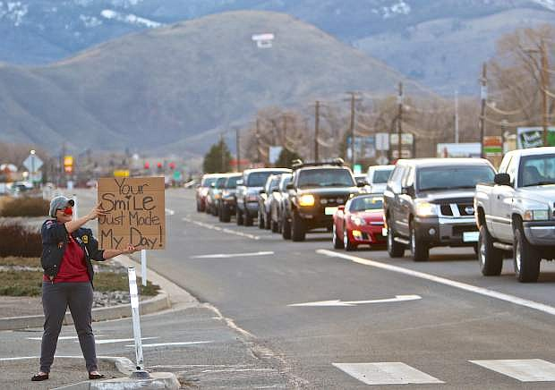 E.D. Crouser of Carson City flashes a homemade sign at drivers as they drive by the intersection of Highway 50 and Fairview Wednesday evening. When asked what motivates her to do what she's doing she simply stated 'because everybody smiles.'