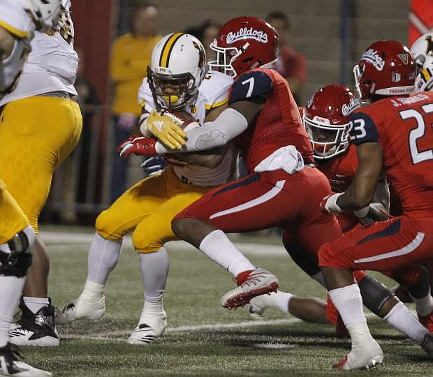 Wyoming running back Nico Evans is bottled up by Fresno State linebacker James Bailey on Saturday in Fresno, Calif. Fresno State beat Wyoming, 27-3.