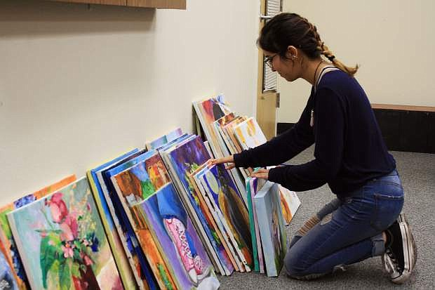 Jazlyn Duran, a senior at CHS, sorts through original oil and acrylic paintings by former Carson artist Carol Benson at the Carson City Senior Center.