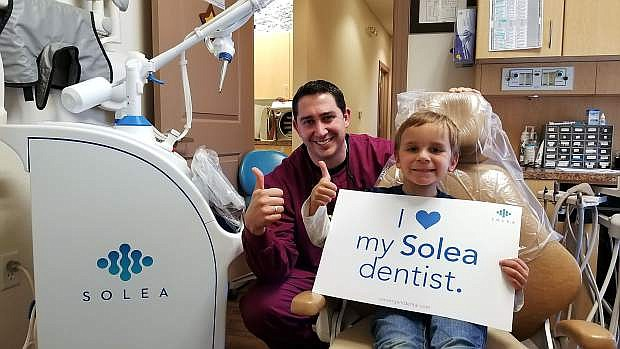 Kevin Olson, DMD, and co-owner of Carson City Pediatric Dentistry, with his patient, Mason, age 5, after a successful dental procedure using the Solea laser.