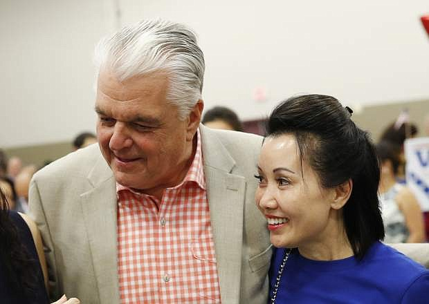 File - In this Aug. 28, 2018 file photo, Clark County Commission member and Democratic gubernatorial candidate Steve Sisolak and Kathy Ong meet others at an event in Las Vegas. Nevada Governor-elect Steve Sisolak is now engaged to be married. The Democrat's campaign on Monday, Nov. 12, 2018, announced the engagement to his girlfriend of more than five years, Kathy Ong. Ong is a financial consultant in Las Vegas. Sisolak and Ong met at their local gym. Details of the wedding were not released. (AP Photo/John Locher)