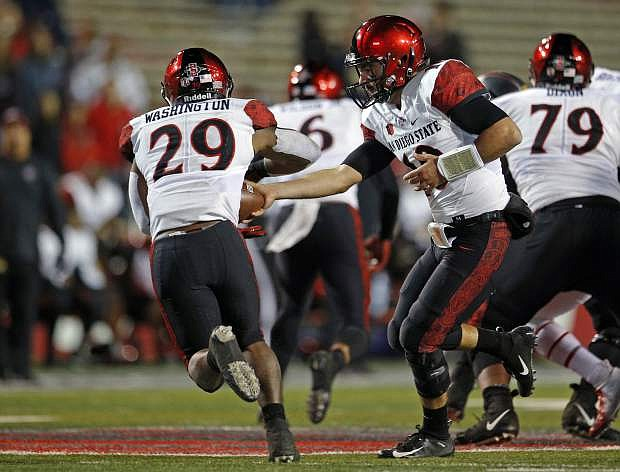 San Diego State running back Juwan Washington (29) takes a handoff from quarterback Christian Chapman (10) during the second half of an NCAA college football game in Albuquerque, N.M., Saturday, Nov. 3, 2018. San Diego State won 31-23. (AP Photo/Andres Leighton)