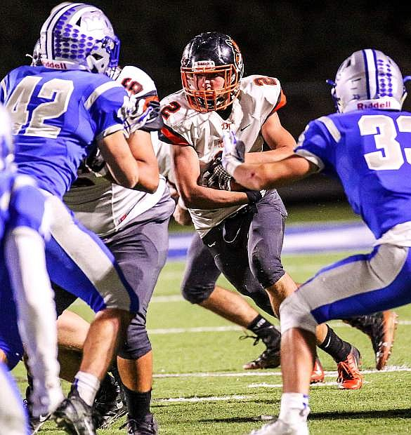 Isaac Leigh carries the ball up the middle for the Tigers on Friday night at McQueen.