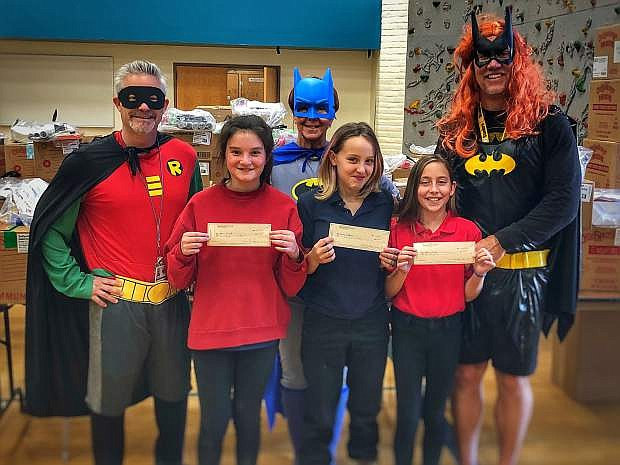 Eagle Valley Middle School administrators Mike Maiello, dean of students (Robin), Dr. Sue Moulden, vice principal (Batman) and Lee Conley, principal (Batgirl), pose with 13-year-old Abby Elliott, eighth grader, who earned $75 for second place, selling 69 units; 12-year-old Drew Coburn, seventh grader, who earned $100 for first place, selling 112 units, and 12-year-old Haley Sisk, sixth grader, who earned $50 for third place, selling 55 units.