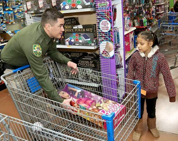 Carson City Sheriff's Office Detective Steve Olson places a Barbie doll in the basket for 6-year-old Zitlalic at Walmart during last year's Holiday With a Hero event. The Holiday Crawl set for Dec. 1 is a fundraiser for Holiday with a Hero.