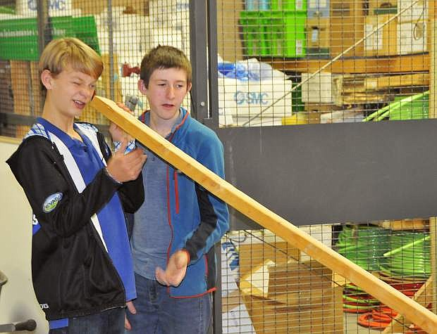 Halen Harrison, left, and Bennett Card check their piece of lumber for warping in their project to build a canoe with the Carson Makers Inventing Tomorrow Club, which meets Mondays in the Construction Shop at Western Nevada College.