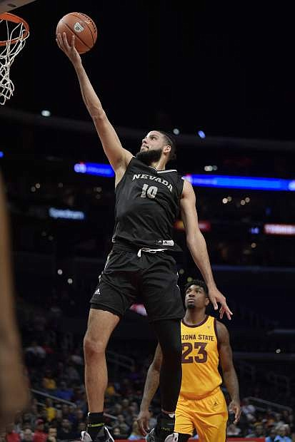Nevada forward Caleb Martin, left, shoots as Arizona State forward Romello White watches during the first half of an NCAA college basketball game at the Basketball Hall of Fame Classic on Friday, Dec. 7, 2018, in Los Angeles. (AP Photo/Mark J. Terrill)