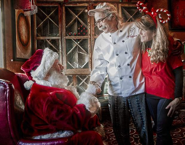 Santa Strekal greets Chef Charlie and Karen Abowd. Santa will appear at the annual Cookies with Santa event Saturday at Cafe at Adele's at 1112 N. Carson St. in Carson City.