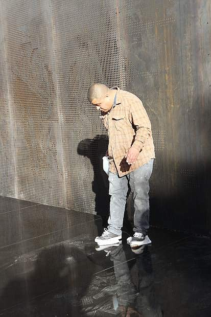 Carlos Iniguez of Premier Tile and Stone goes across the new marble surface of the Battle Born Memorial honoring Nevada's fallen veterans, polishing it with cloths soaked in Acetone under his shoes.