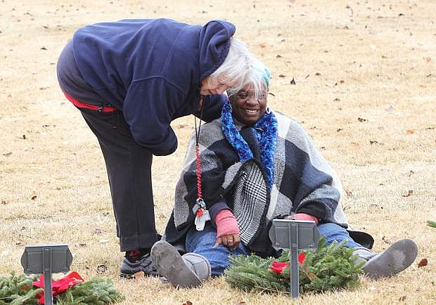 A woman comforts a mourner who sits in front of a gravesite.