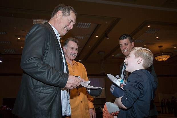 San Francisco Giants manager Bruce Bochy, left, signs a few hats for 12-year-old Matt Campell while best-selling author Kevin Freiberg (back, left) and University of Nevada manager T.J. Bruce look on before the 34th-annual Bobby Dolan Baseball Dinner on Thursday at the Reno Ballroom.